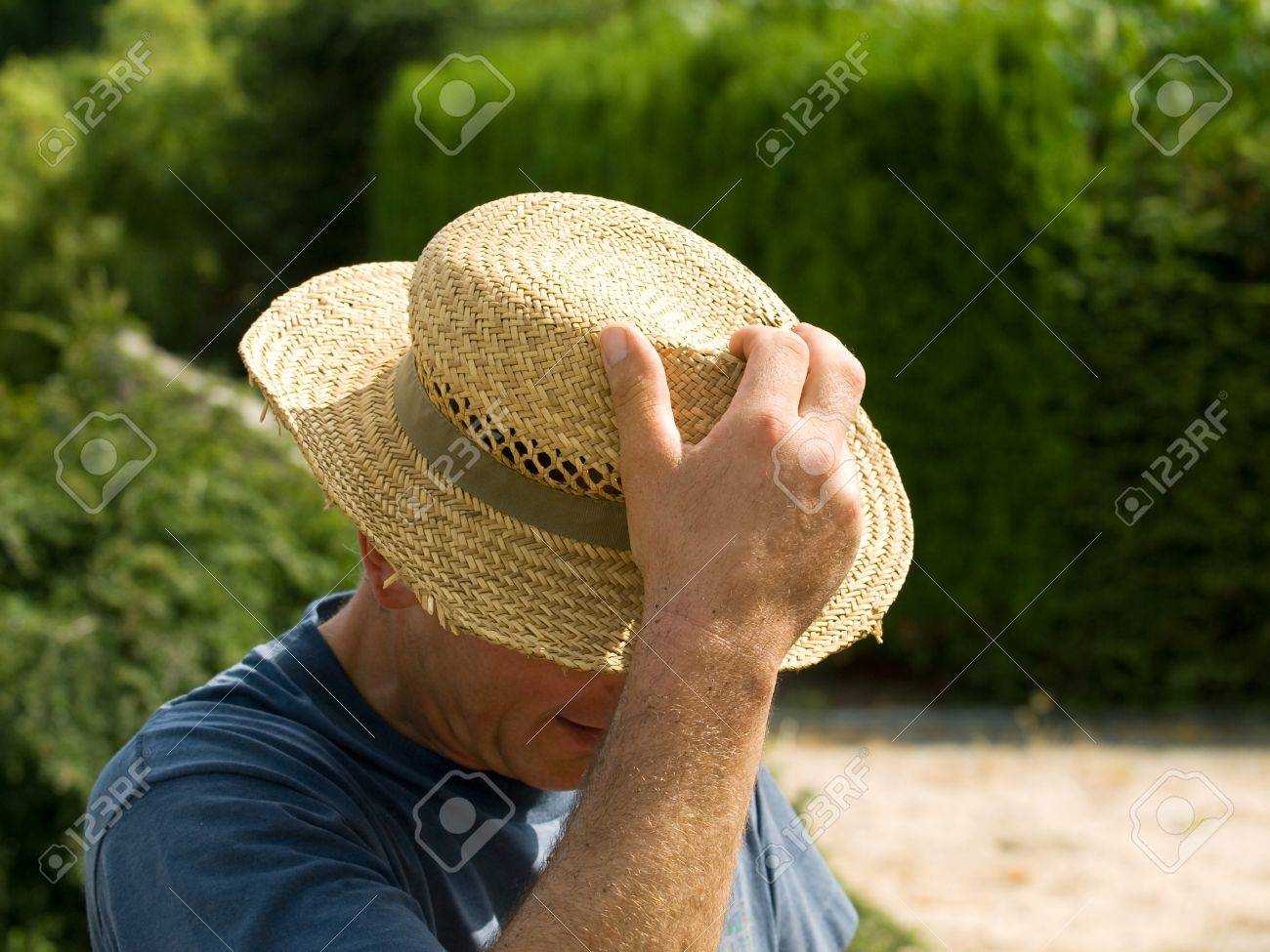 Men taking off his straw hat Stock Photo - 10258470