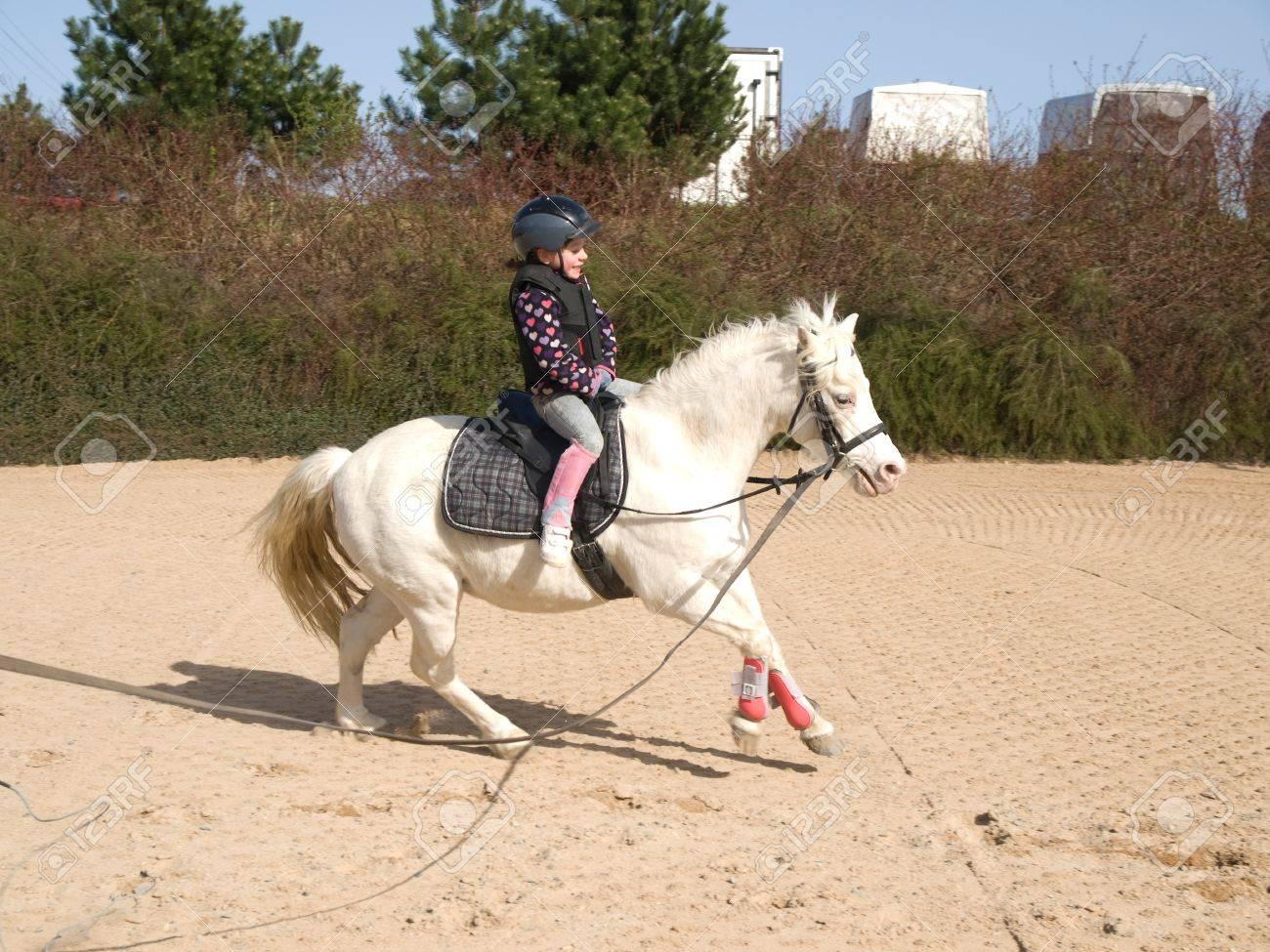 Little girl on galloping white ponny Stock Photo - 11242982