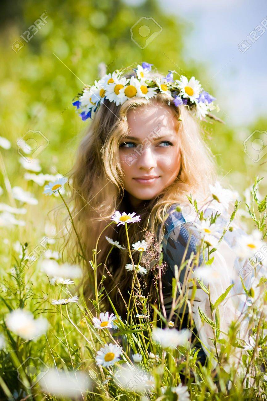 Beautiful young girl with diadem on camomile field - 6445897
