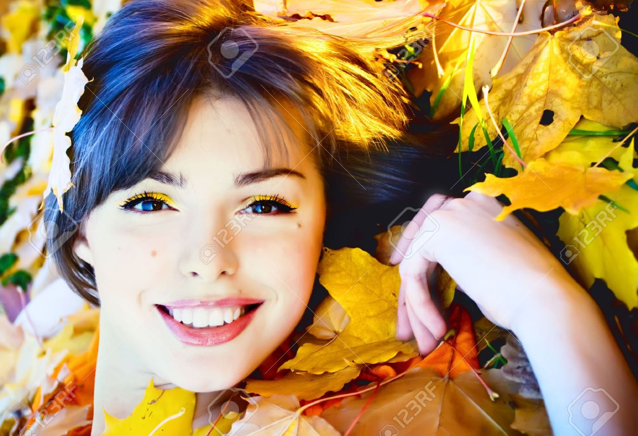 Beautiful smiling young woman in autumn leaves - 8171278