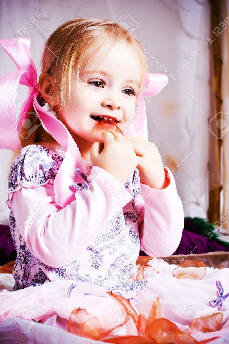 Beautiful little girl play on white bad Stock Photo - 8781988