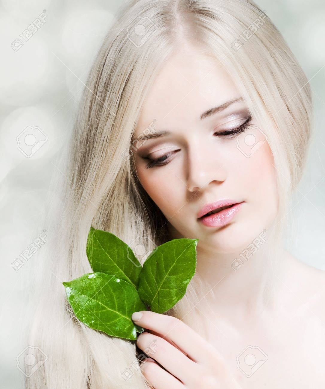 Beautiful young girl with healthy skin and green leaf - 11034653