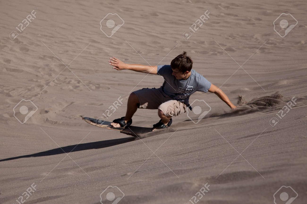 A teenage boy sandboarding at the Great Sand Dunes National Park