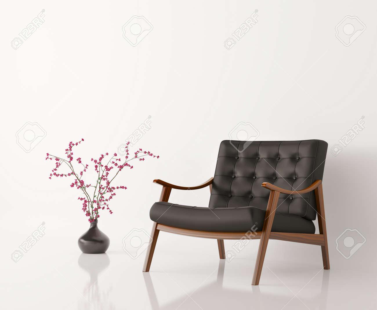 Zwart lederen fauteuil en bloem vaas tegen witte muur geïsoleerde