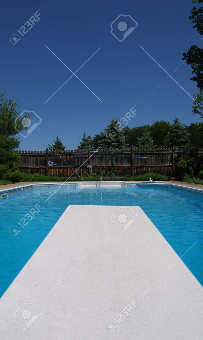 view off the diving board of a backyard pool showing pool