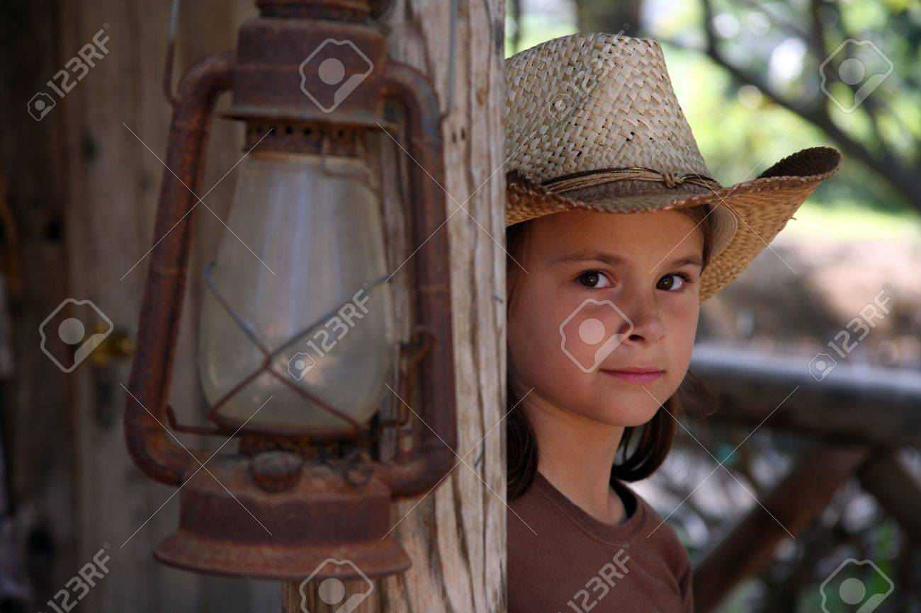 Young cowgirl looking around a wooden post Stock Photo - 823881