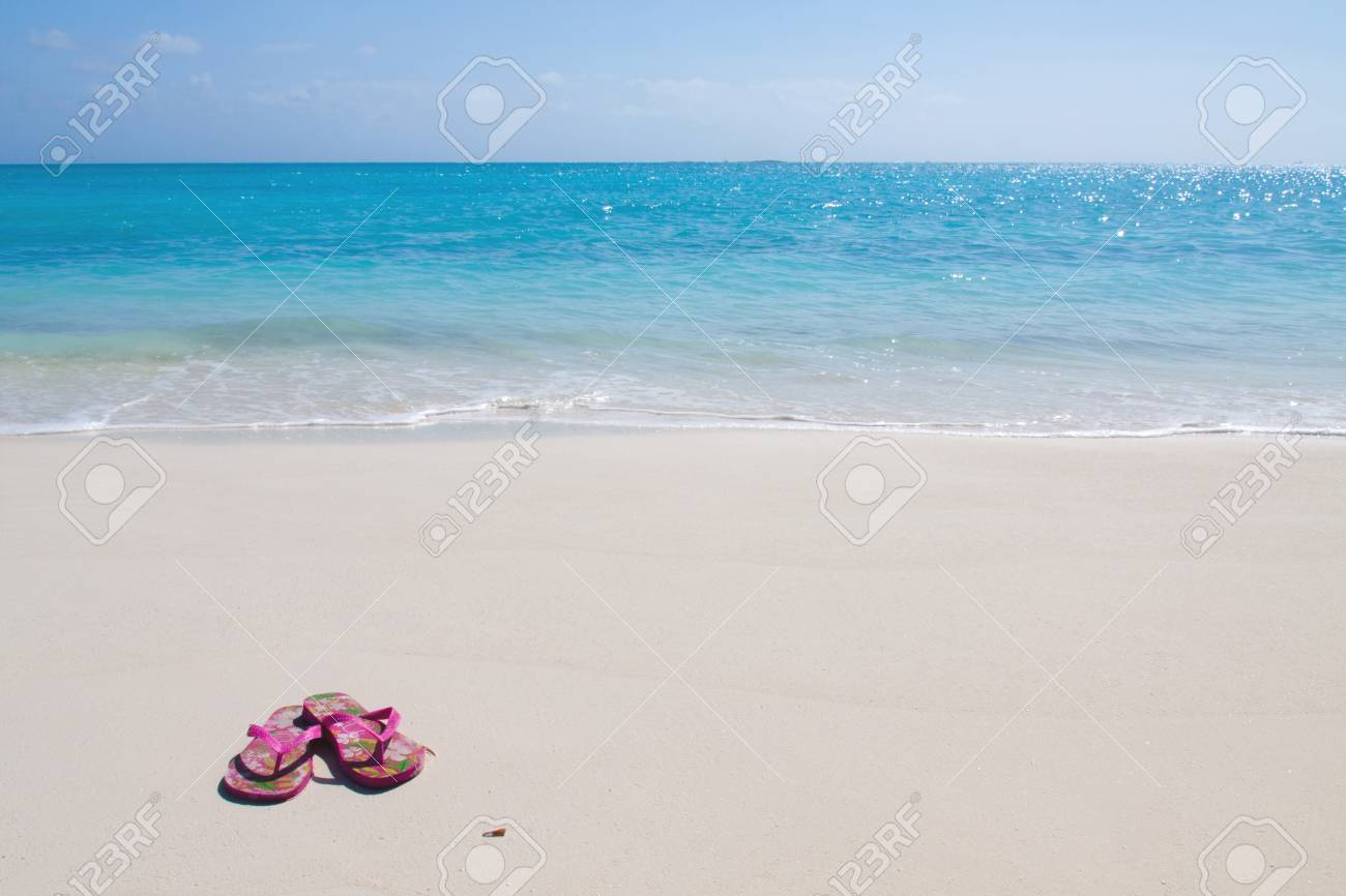 fb328e93f Pair of colored sandals on a white sand beach in front of the sea. The