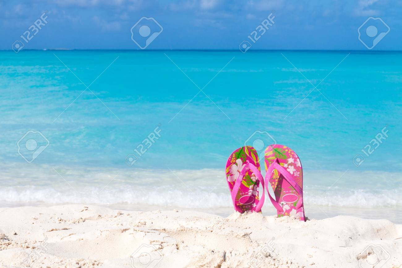 94740f1db Pair of colored sandals on a white sand beach in front of the sea Stock  Photo