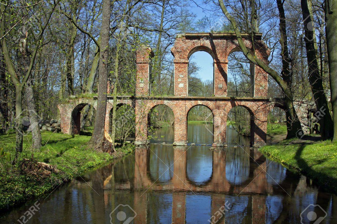 antique roman aqueduct reflecting in a pool of water stock photo