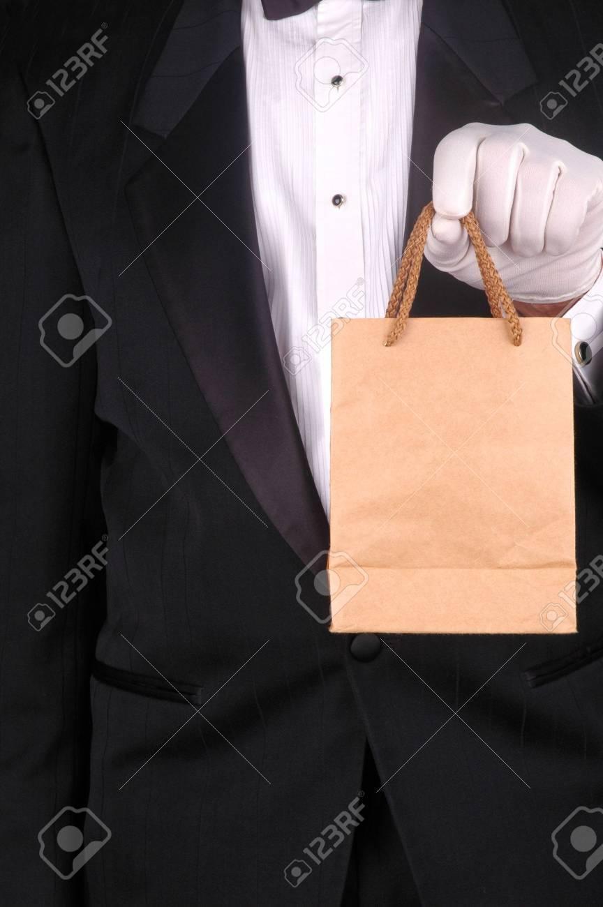 Man in Tuxedo Holding a Small Brown Bag - torso shot Stock Photo - 2995306