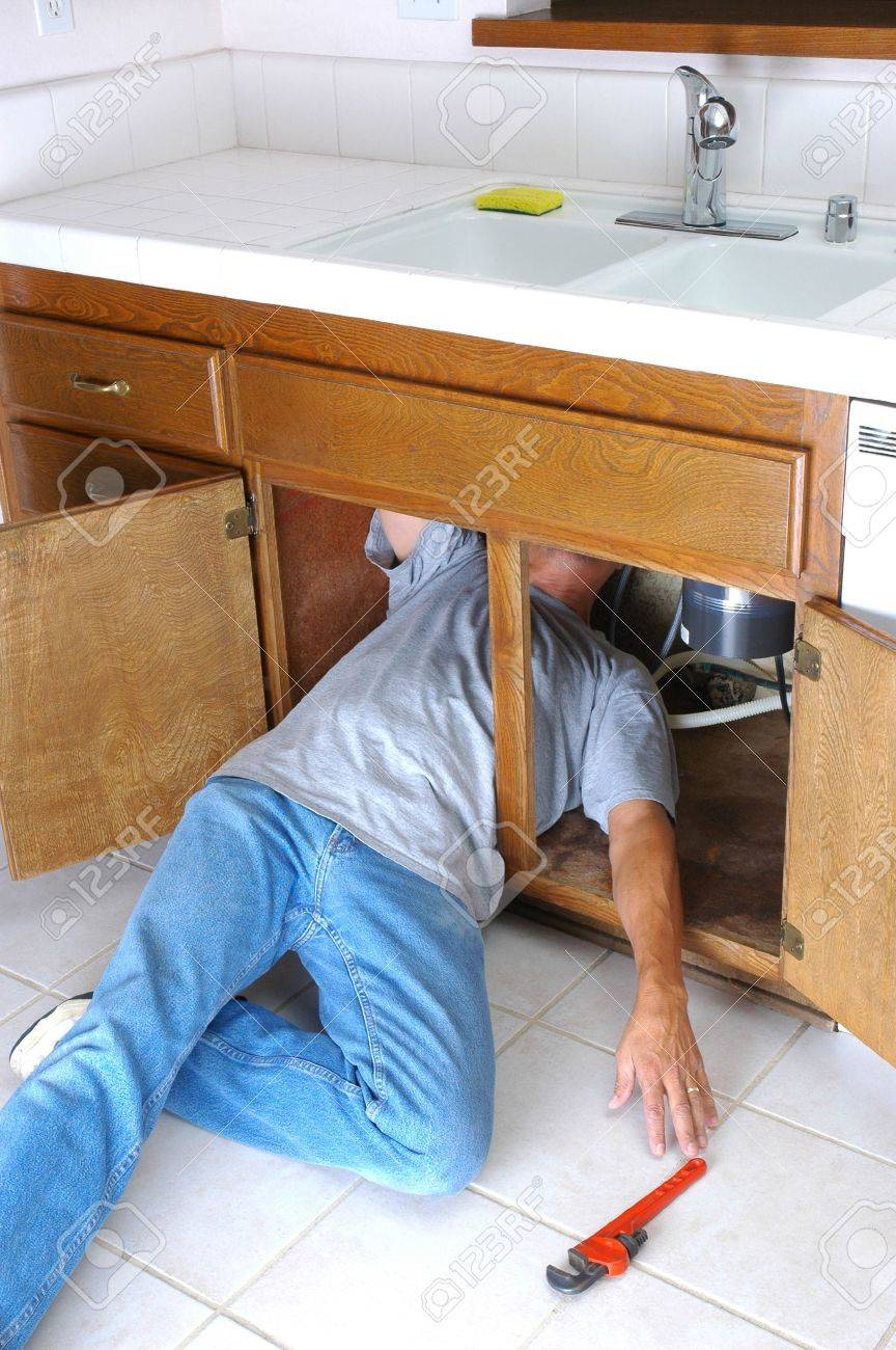 man under kitchen sink reaching for pipe wrench stock photo 3675737 - Kitchen Sink Wrench