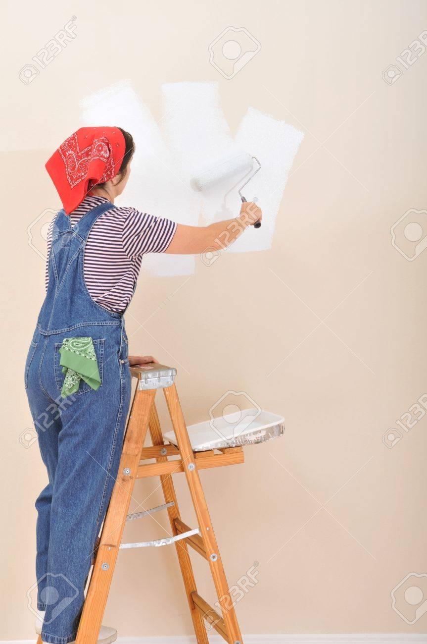 mujer en escalera utilizando el rodillo para pintar el interior de su foto de archivo