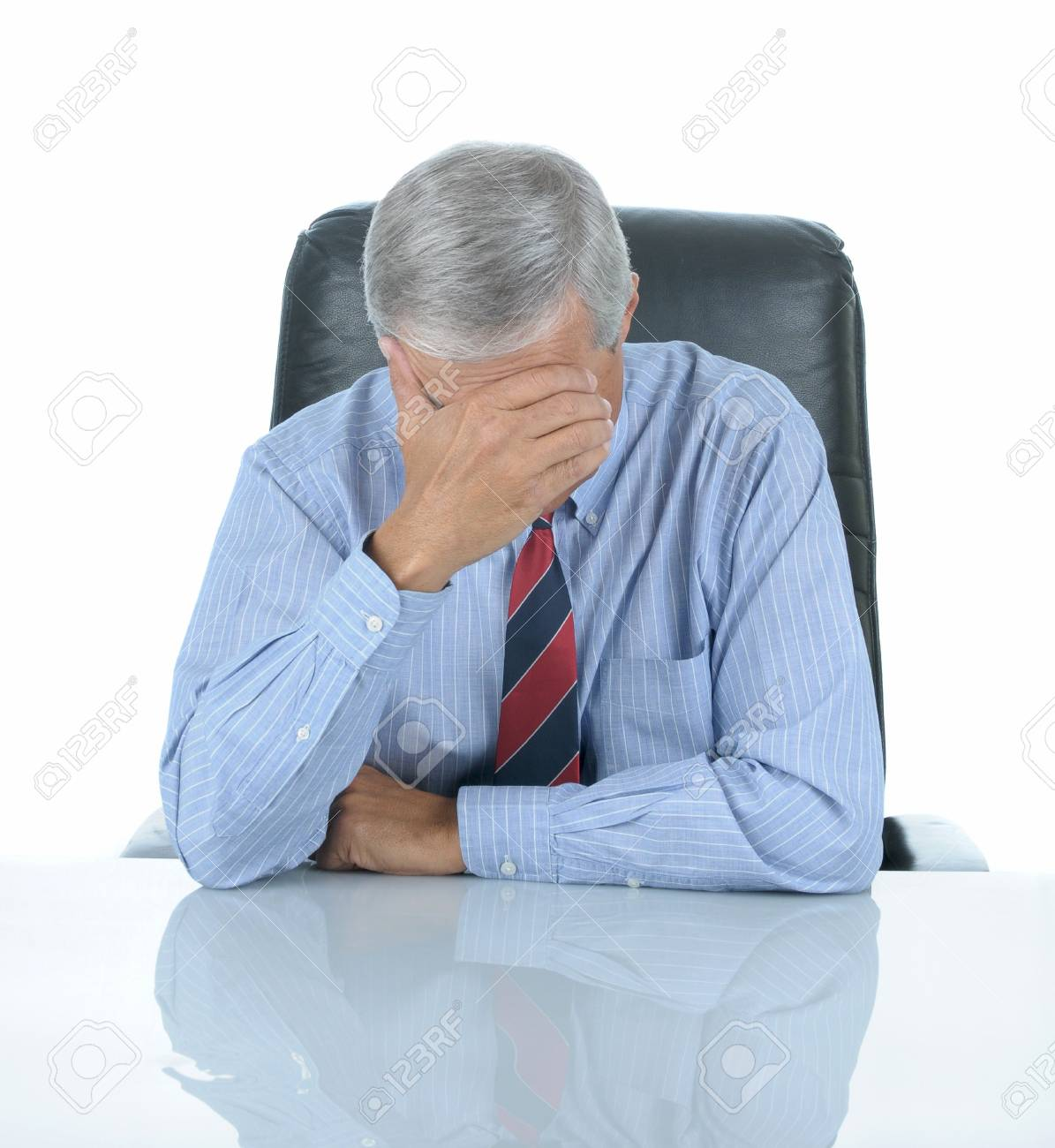Middle aged businessman seated at his desk with his head in his hand. Square format isolated on white with reflection in desk top. Stock Photo - 7562322