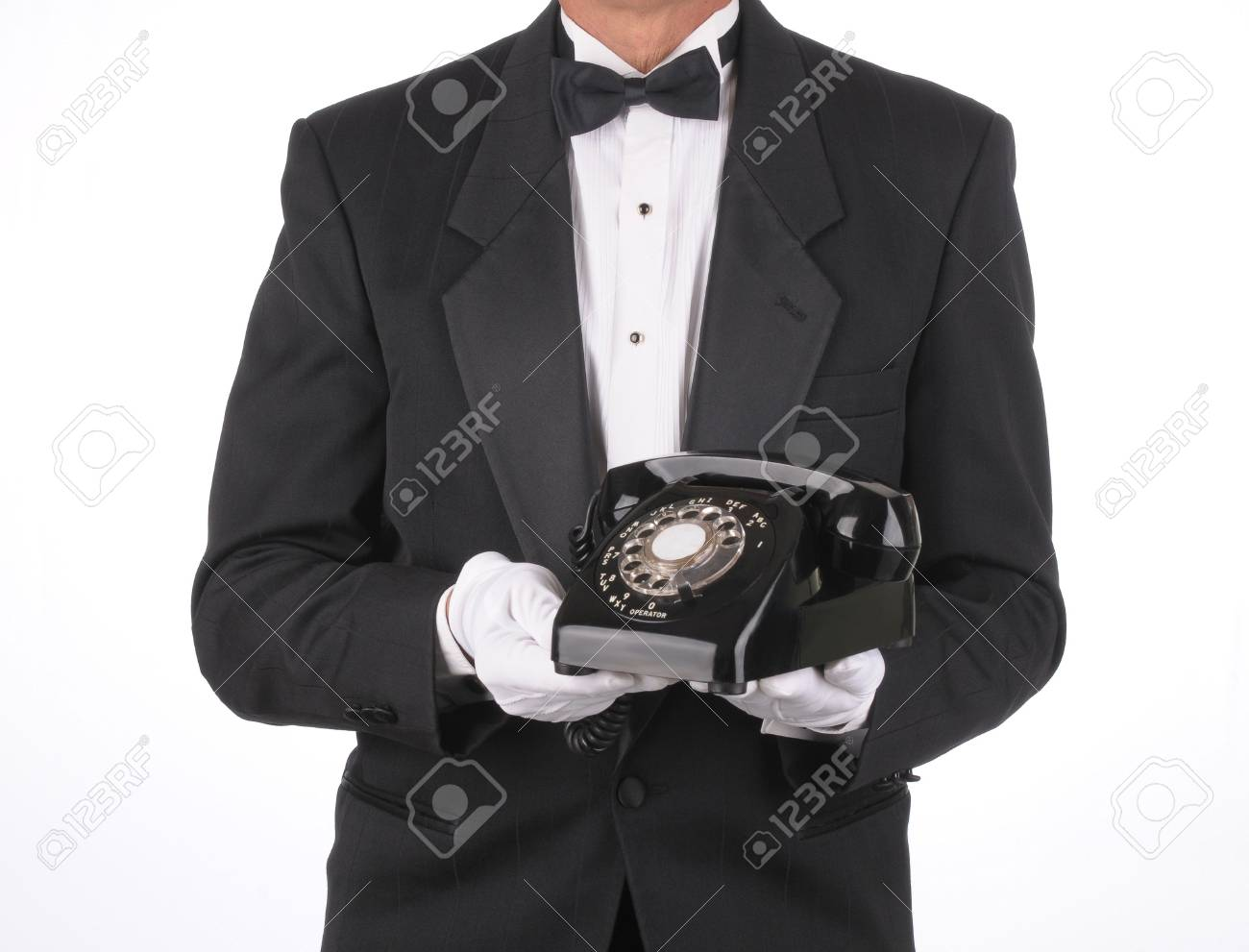 Butler in Tuxedo holding an old rotary telephone in front of his body. Torso shot only isolated over a white background. Stock Photo - 8094206