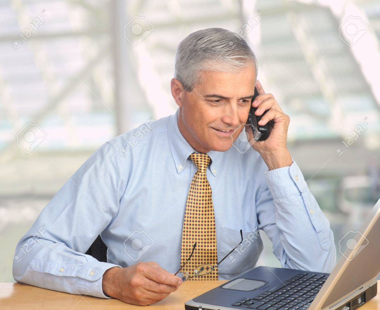 Middle aged businessman with laptop talking on telephone in modern office setting. Square format. Stock Photo - 8610060