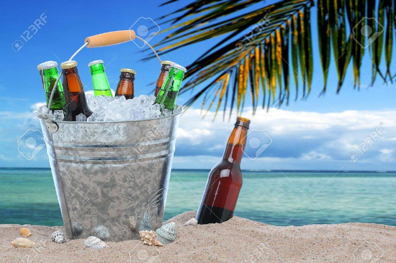 Assorted beer bottles in a bucket of ice in the sand on a tropical beach. One beer bottle without a cap is by itself stuck in the sand next to the pail. Stock Photo - 8680589
