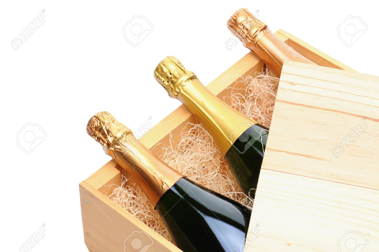 Closeup of three Champagne bottles on their side in a wooden crate. Crate lid is pulled partially back exposing the bottles and packing excelsior. Horizontal format isolated on white. Stock Photo - 9961104
