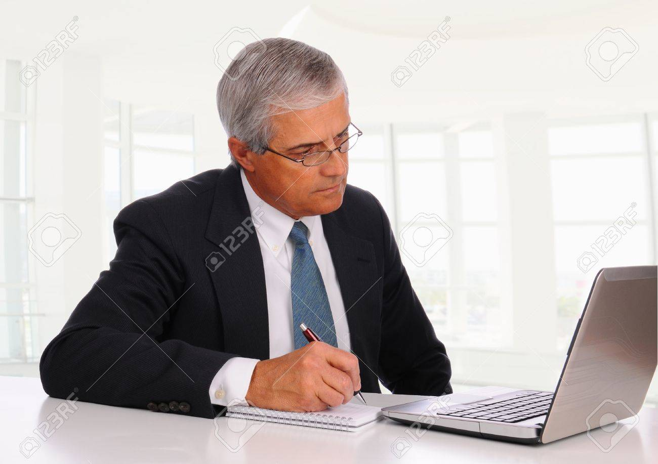 Smiling Middle Aged Businessman at desk using laptop computer with concerned expression. Horizontal format in modern office setting Stock Photo - 10293387