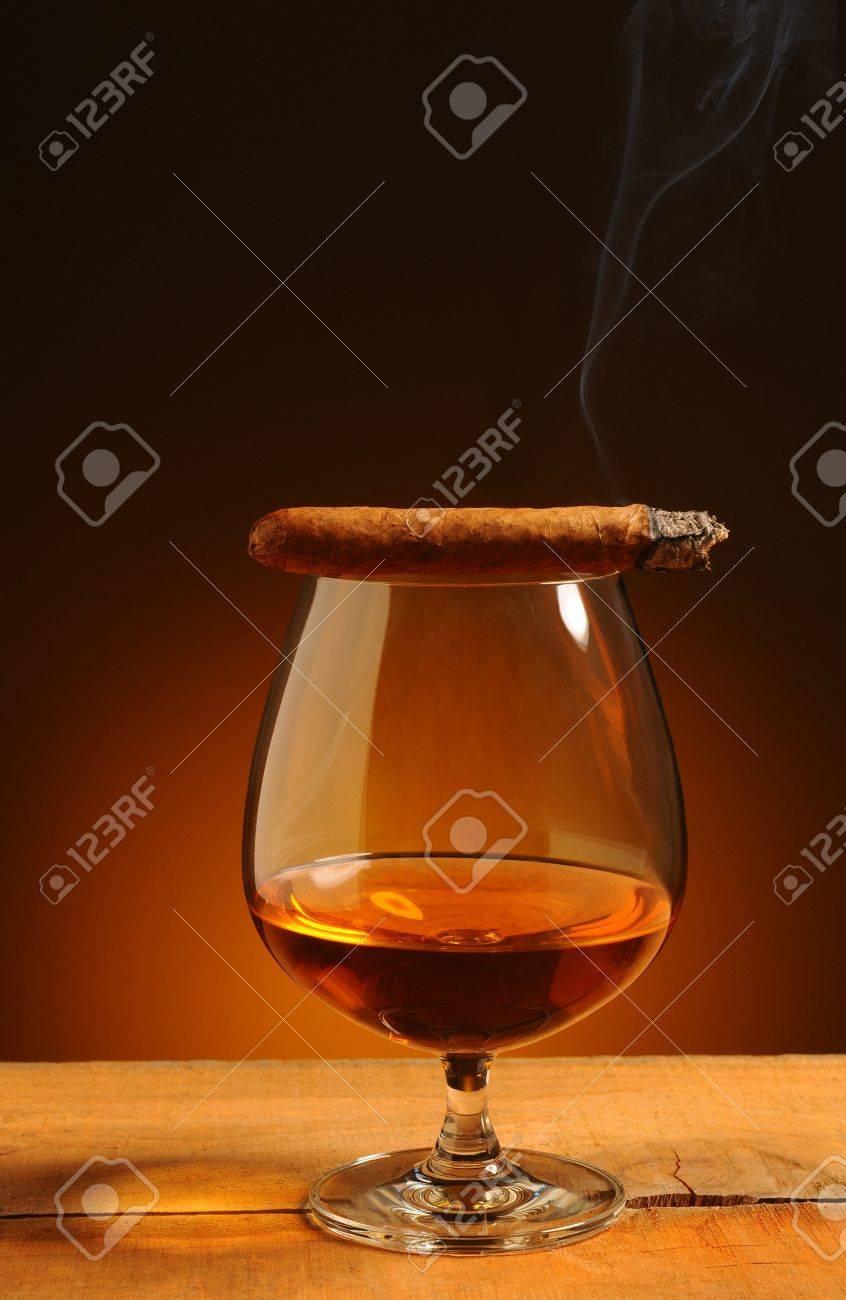 Vetro brandy con un sigaro acceso sul suo bordo su un fondo caldo ...