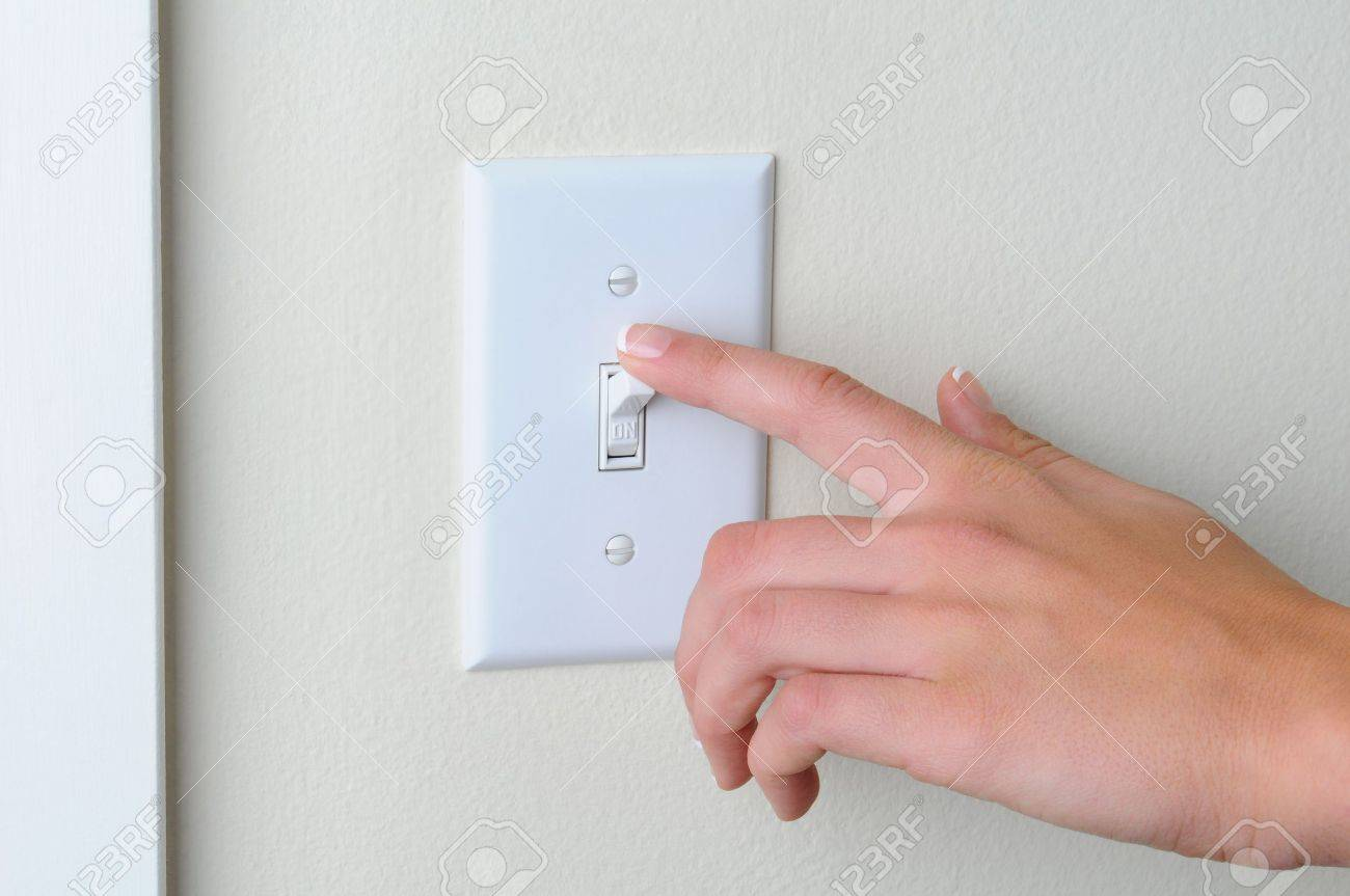 Womans Hand With Finger On Light Switch, About To Turn Off The ...