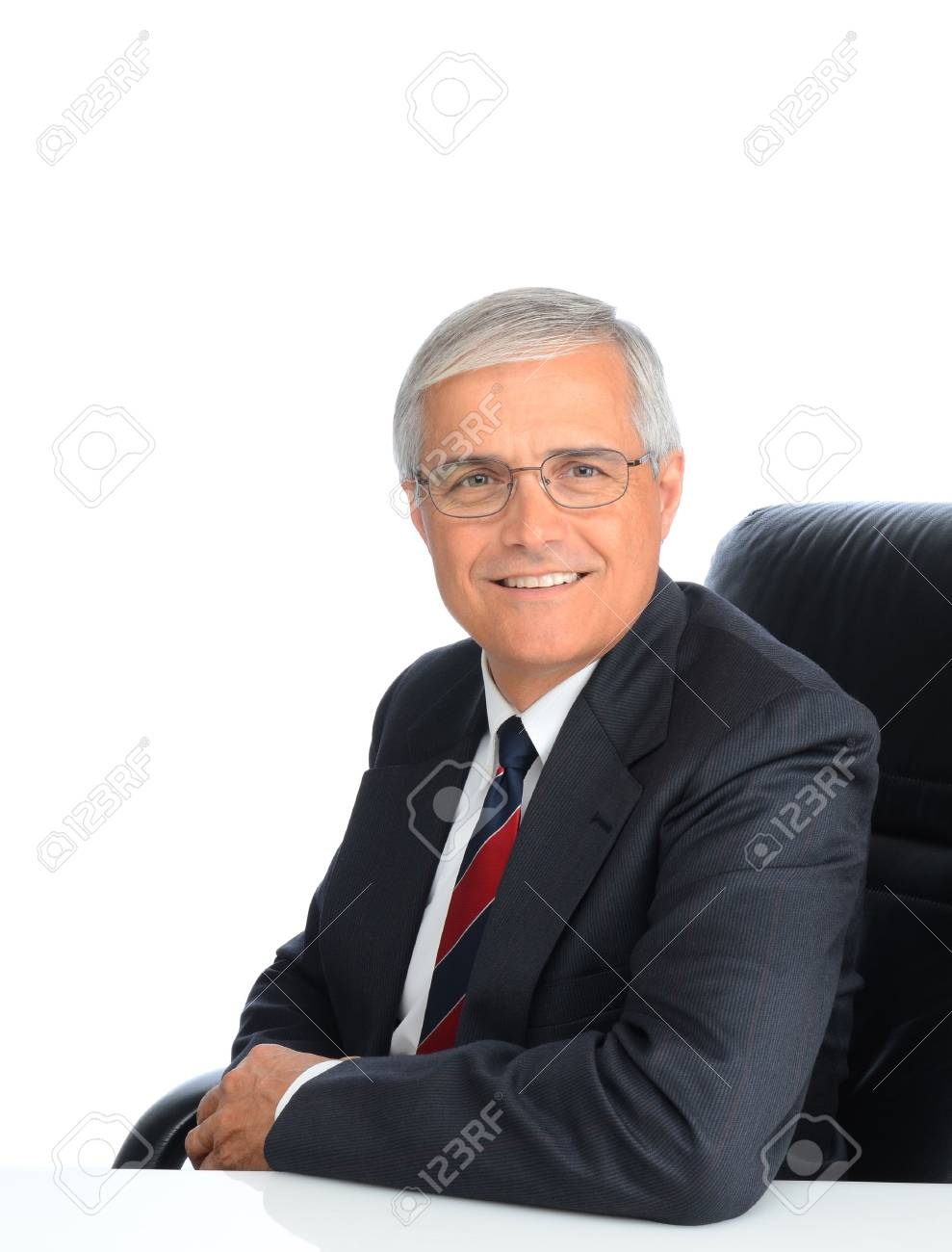 Portrait of a seated mature businessman. Man is smiling and wearing eyeglasses, over a white background. Stock Photo - 13467405