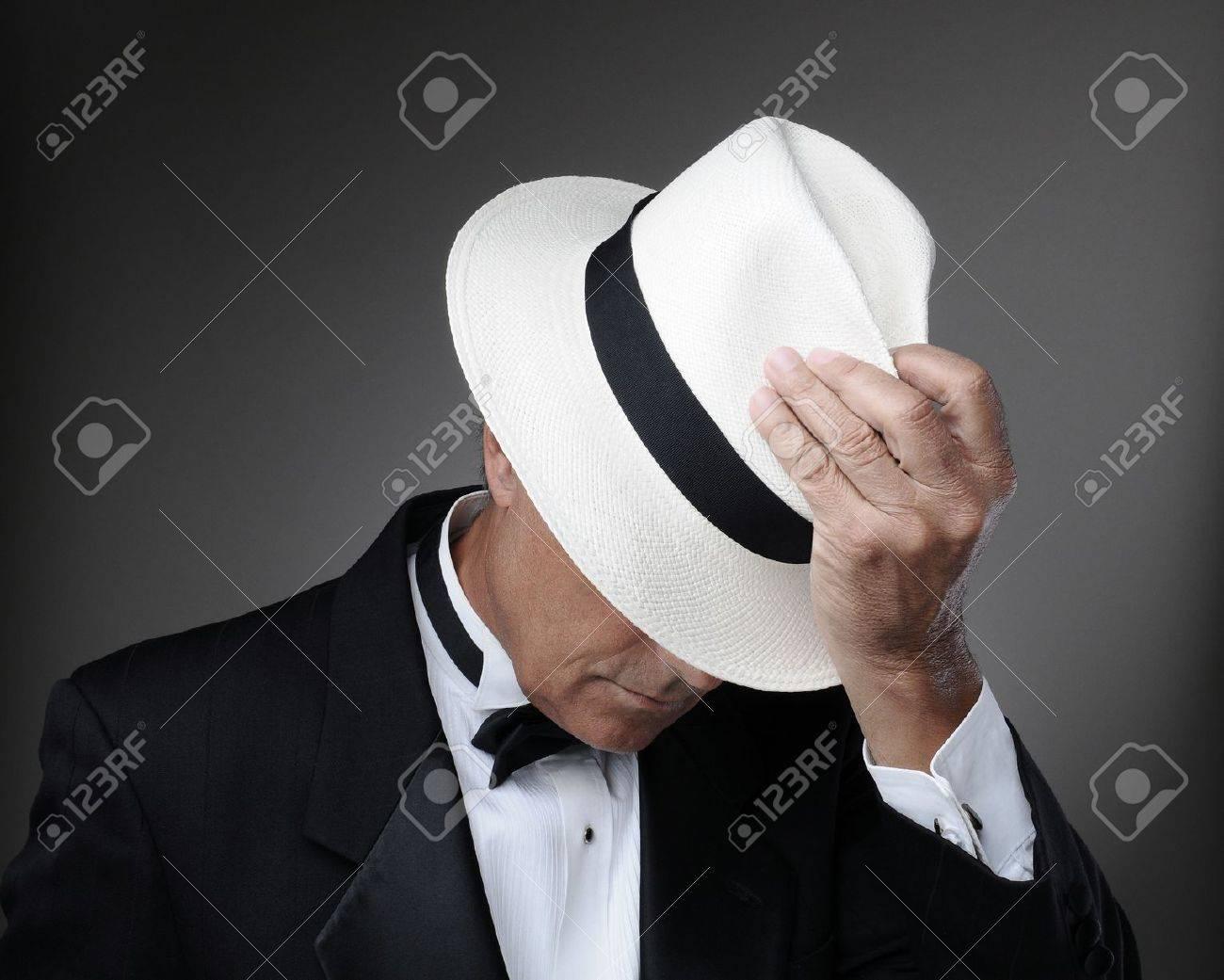 Archivio Fotografico - Primo piano di un uomo di mezza età che indossa uno  smoking e un cappello Panama. Orizzontale su uno sfondo grigio. 26f500698edd