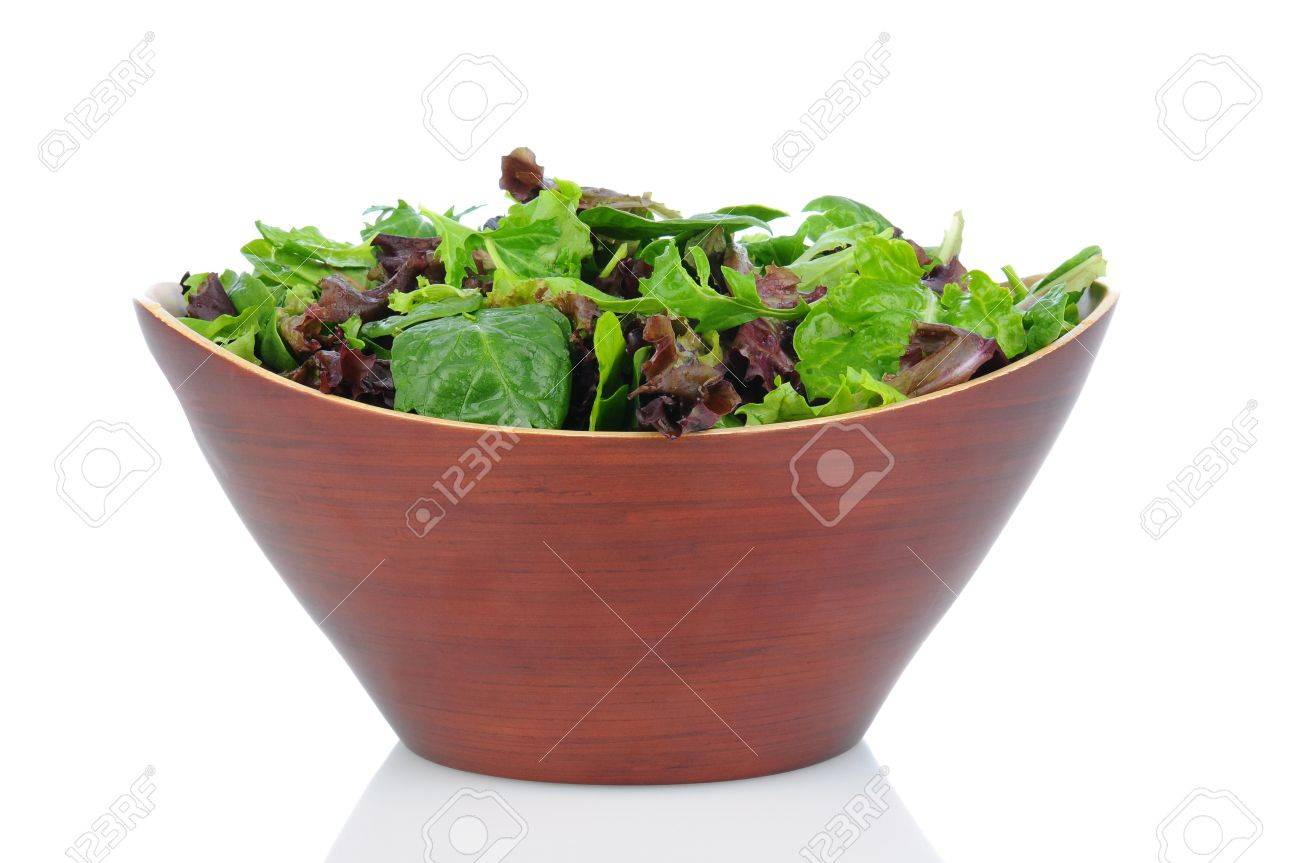 A Wooden bowl full of assorted salad greens, including, spinach, arugula, and romaine. Horizontal format on a white background. Stock Photo - 15845491