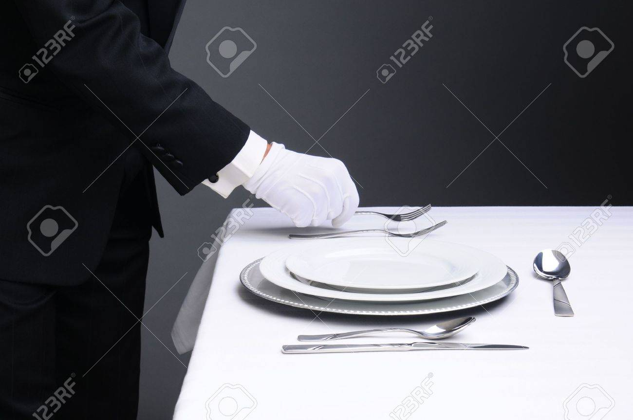 Closeup of a waiter in a tuxedo setting a formal dinner table. Horizontal format on a light to dark gray background. Man is unrecognizable. Stock Photo - 16242313