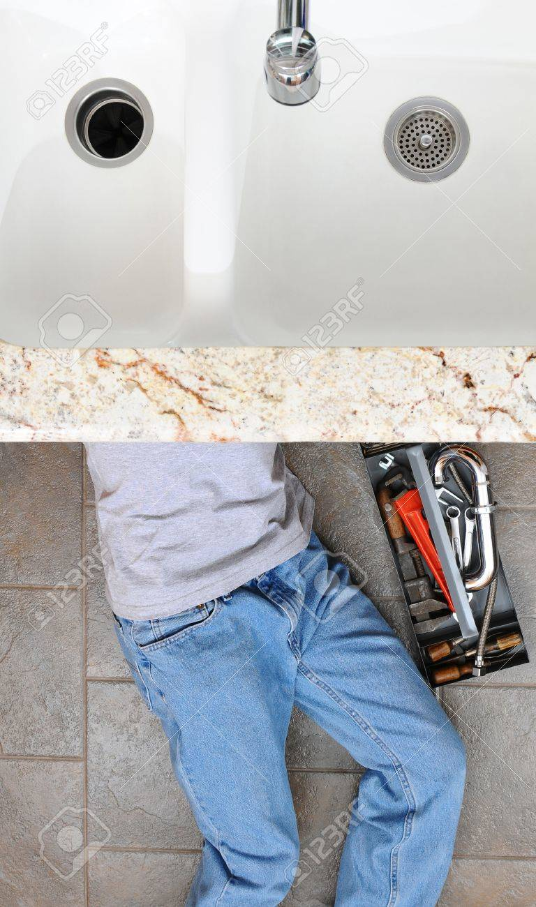 High angle view of a plumber laying under a kitchen sink. Man is unrecognizable with a tool box next to him. Stock Photo - 18871396