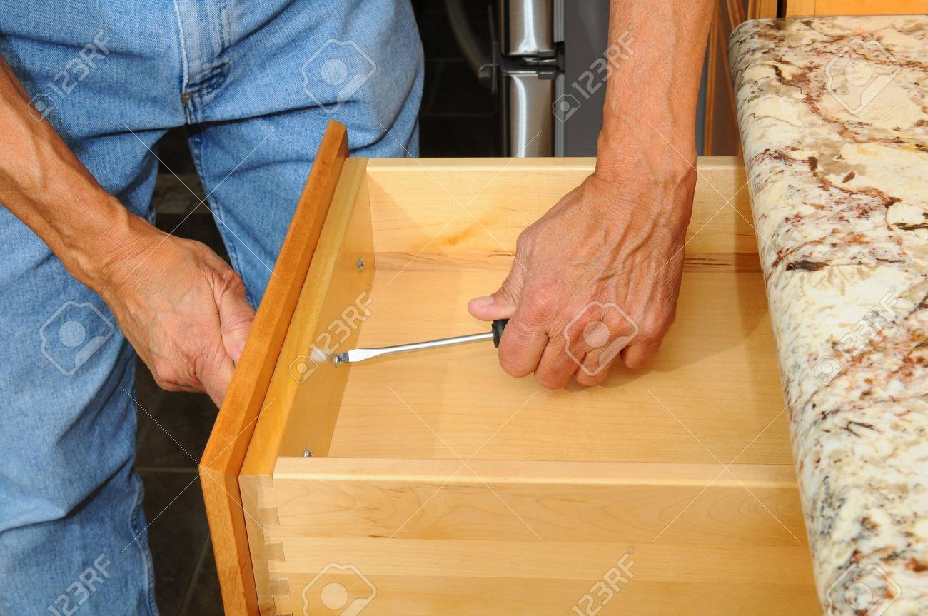 Closeup Of A Cabinet Installer Installing Drawer Hardware On