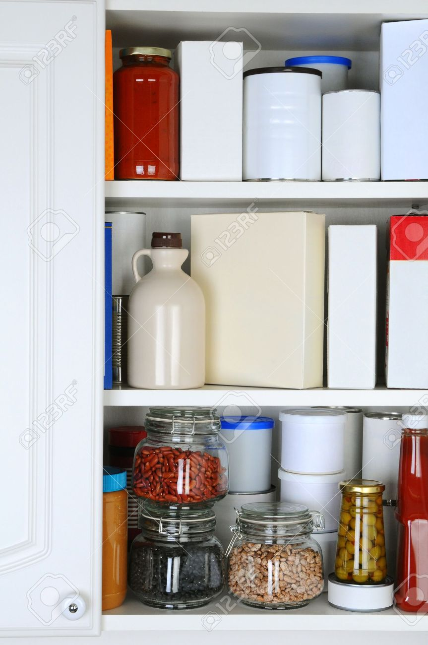Closeup of a well stocked pantry. One door of the cabinet is open revealing canned goods, condiments, package foodstuffs, and storage jars. Stock Photo - 20239654