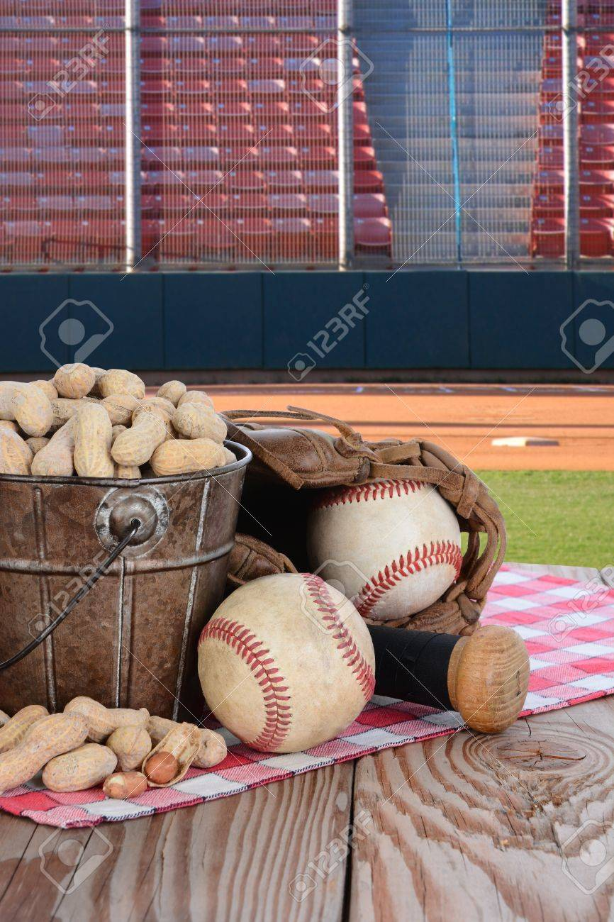 A bucket of peanuts and baseball equipment on a wood picnic table..