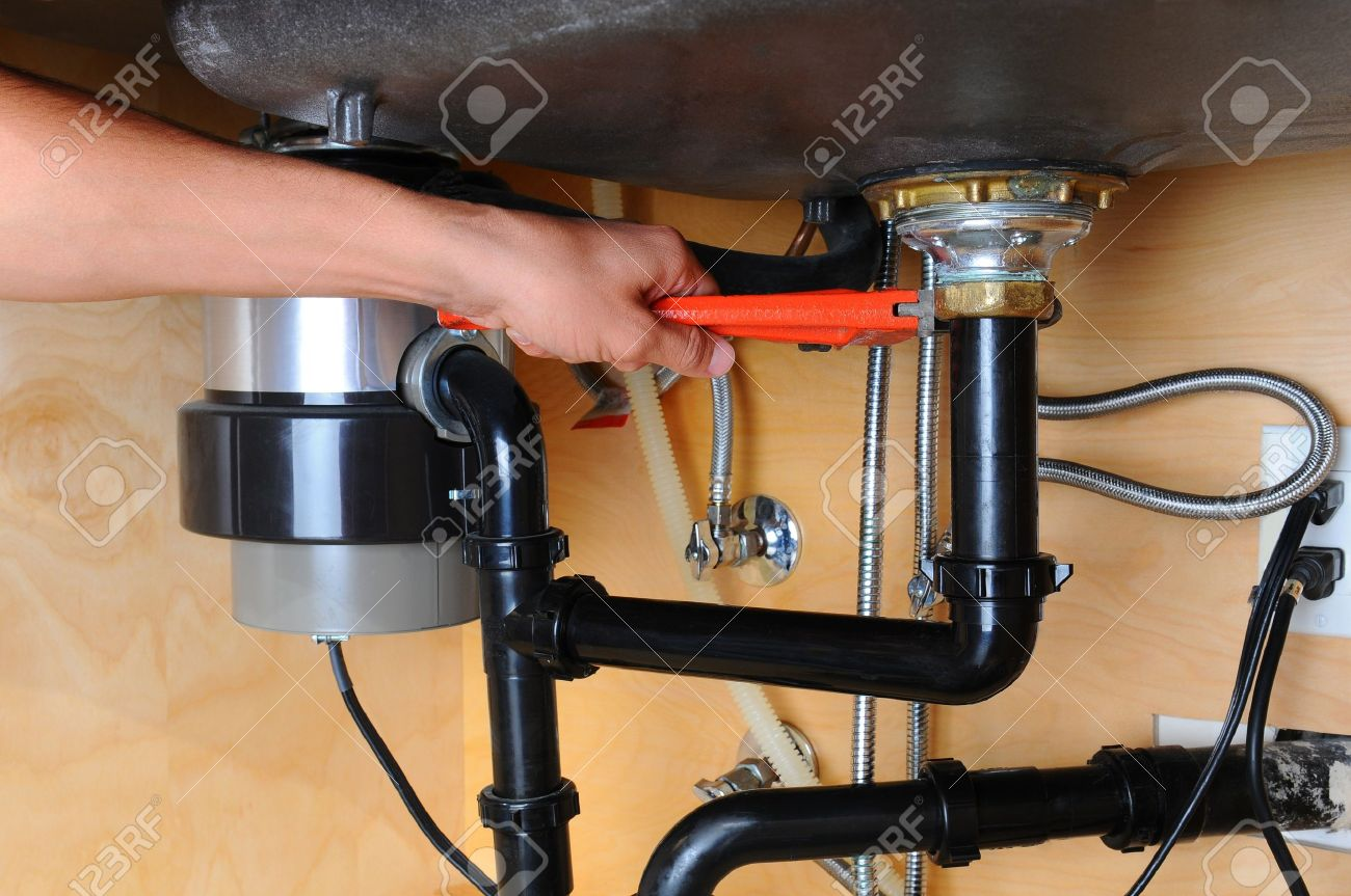 closeup of a plumber using a wrench to tighten a fitting beneath a kitchen sink only - Fitting Kitchen Sink