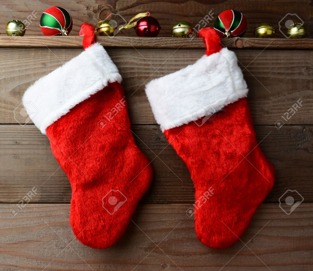 Stock photo two christmas stockings hung on a rustic wooden wall with sliegh bells and ornaments