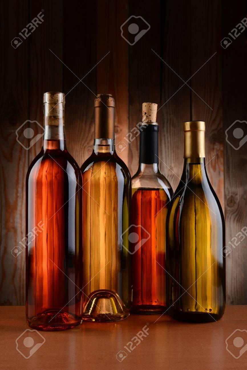 Quatre Bouteilles De Vin Sur Un Fond De Bois Les Bouteilles Nont Aucune étiquette Et La Texture De Larrière Plan Montre à Travers Le Format Vertical
