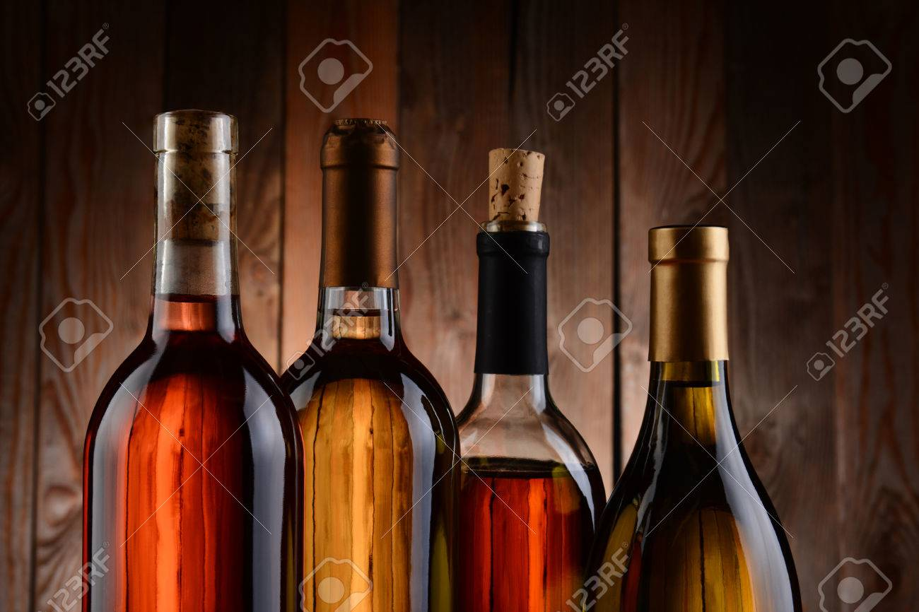 Four wine bottles against a wood background  The bottles have no label and the texture of the background shows through  Horizontal format  showing only the top of the bottles Stock Photo - 23121770