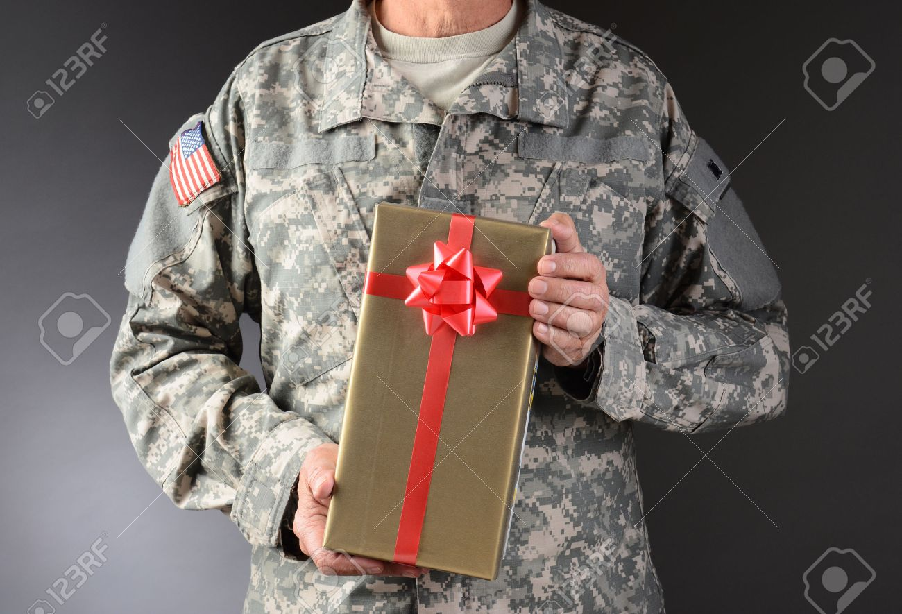 closeup of a soldier holding a christmas present the gift is
