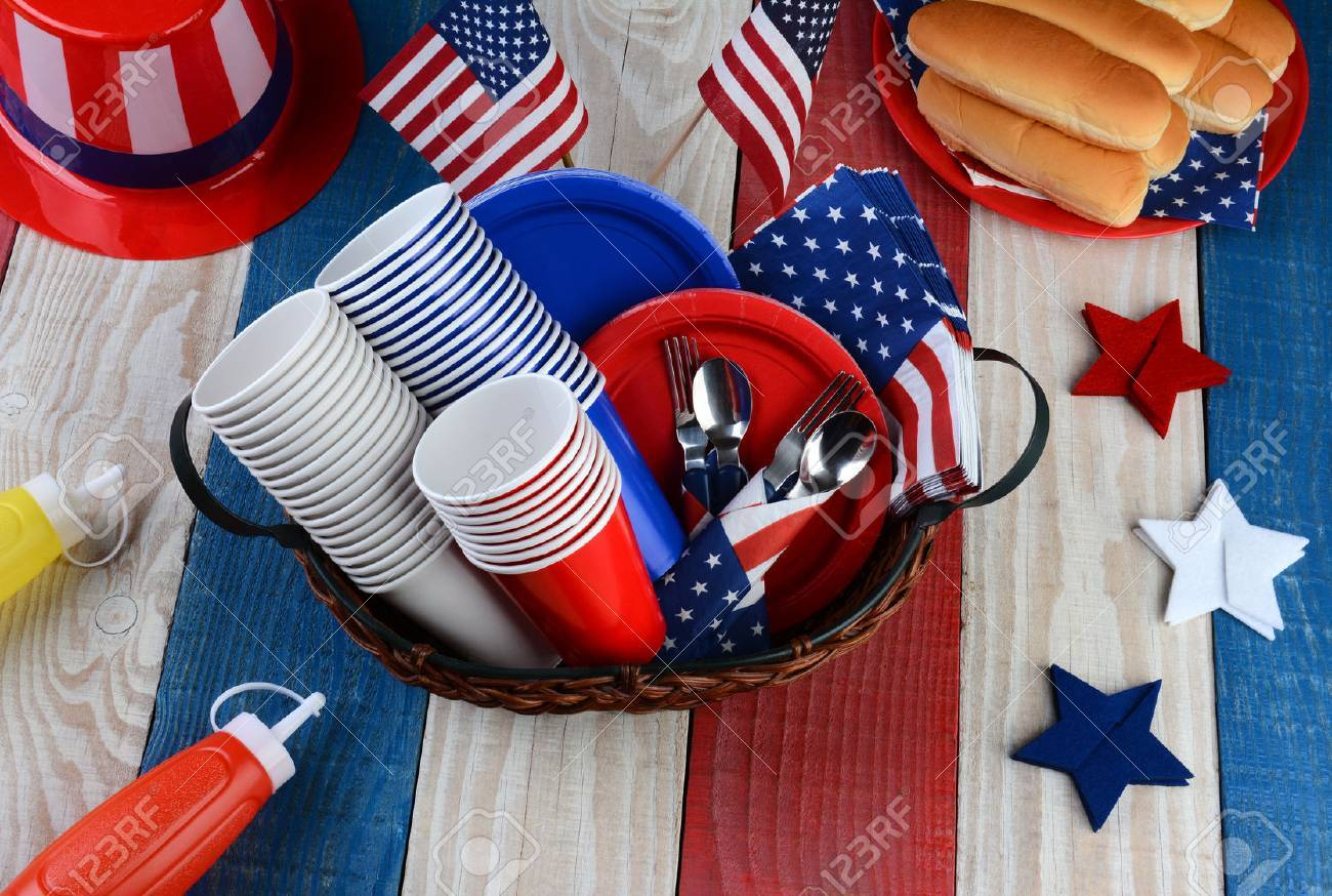 High angle photo of a picnic table ready for Fourth of July Party. The red white and blue table is set with plates, cups, hot dog buns, cups, forks, Uncle Sam Hat, Ketchup and Mustard dispensers. Stock Photo - 27307113