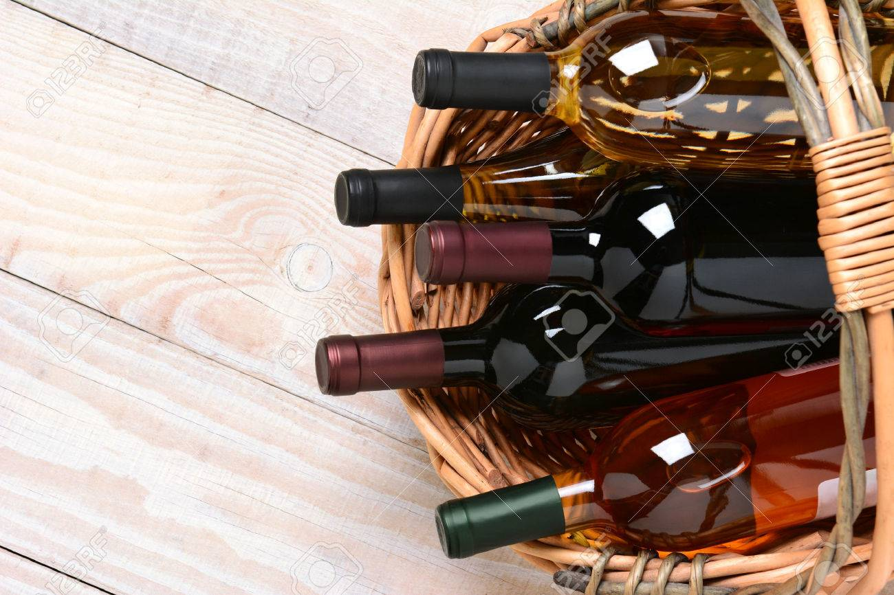 A high angle shot of wine bottles in a basket on a whitewashed wood farmhouse style kitchen table. Horizontal format with copy space. - 30897839