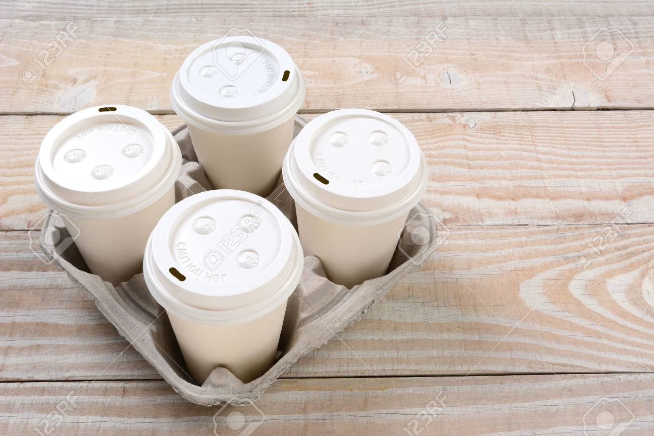 High angle shot of a cardboard take out tray with four coffee cups with lids. - 31285220