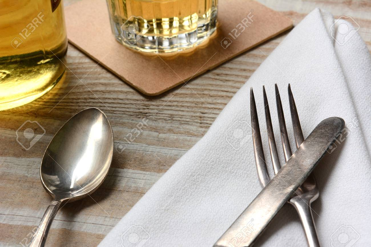 Closeup of a table setting. Old silverware napkin and drinks on a white wood & Closeup Of A Table Setting. Old Silverware Napkin And Drinks ...