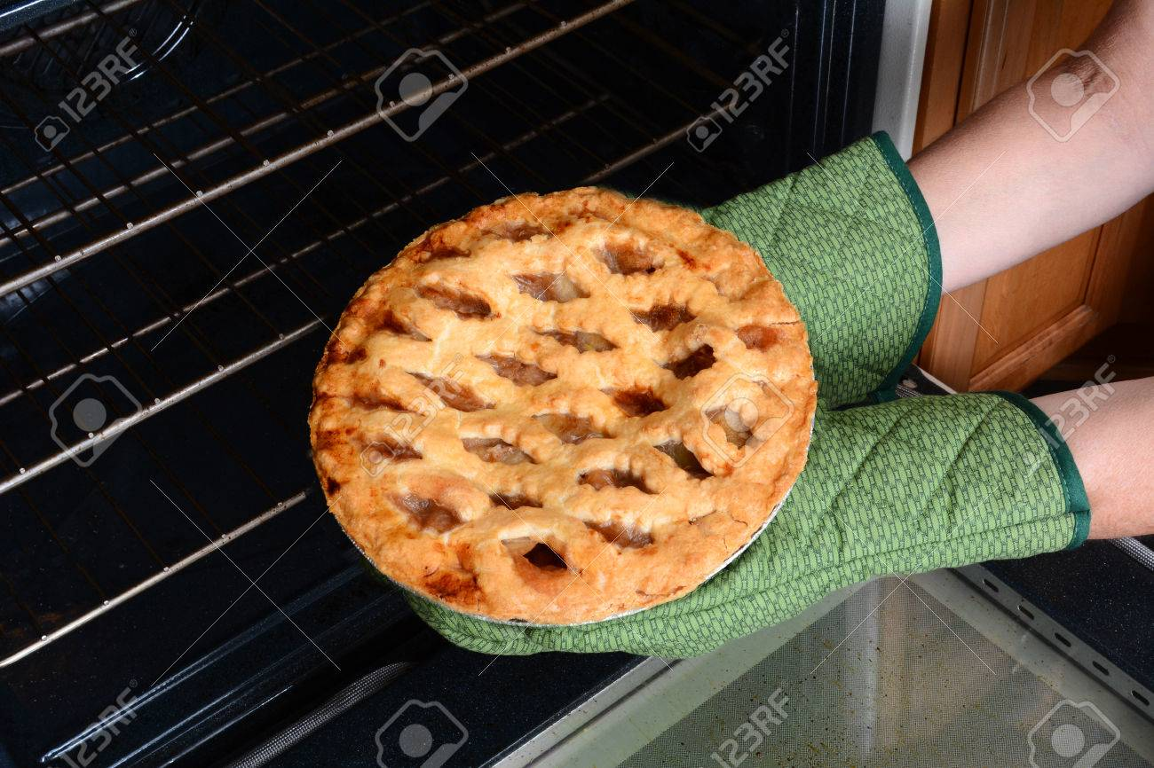 Closeup of a woman taking a fresh baked apple pie from the oven. Apple Pie is a traditional American dessert for Holiday feasts. Horizontal showing the womans hands in oven mitts only. - 33439032
