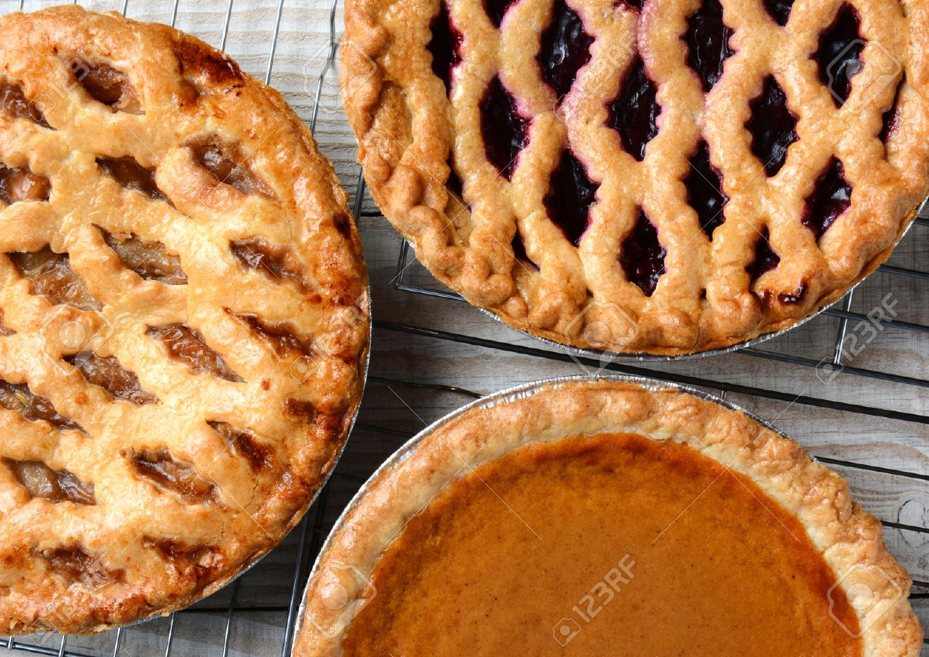 Three pies on cooling racks. High angle closeup shot of fresh baked apple, cherry and pumpkin pies on wire racks on a rustic wood kitchen table. Horizontal format. - 33646397