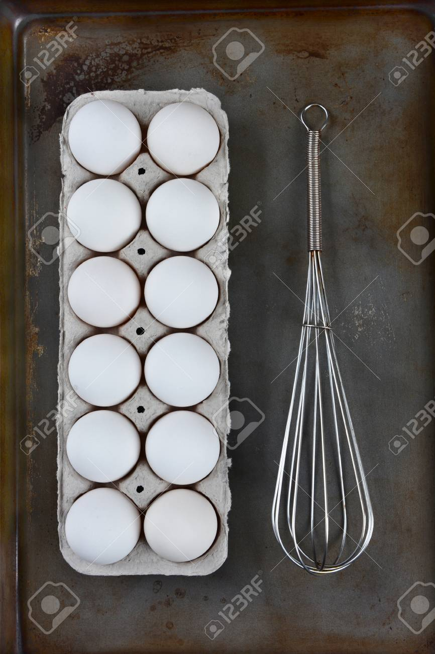 A Carton Of Eggs And A Wire Whisk On A Metal Baking Sheet Stock ...