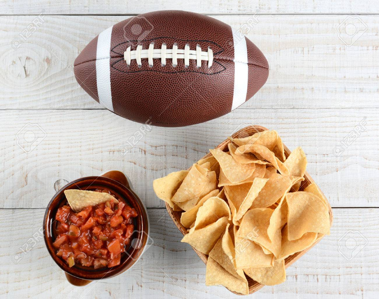 High angle shot of a bowl of corn chips a crock full of fresh salsa and an American football on a whitewashed rustic wood table. Horizontal format. - 35329370