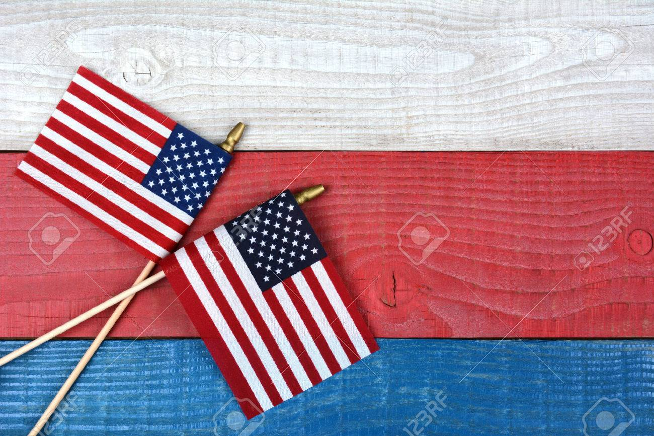 High angle shot of two crossed American flags on a red, white and blue picnic table. Horizontal format with copy space. - 36306567