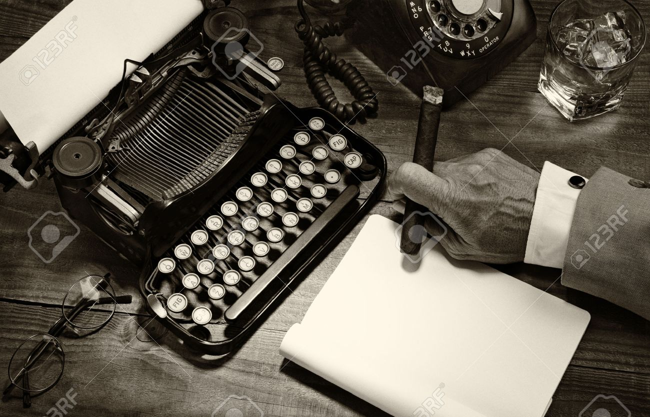 Closeup of a writer at his desk with a typewriter, rotary telephone, glass of whiskey and a cigar. Black and white toned image for a vintage feel. Only the mans hand holding a cigar is shown. - 36499264