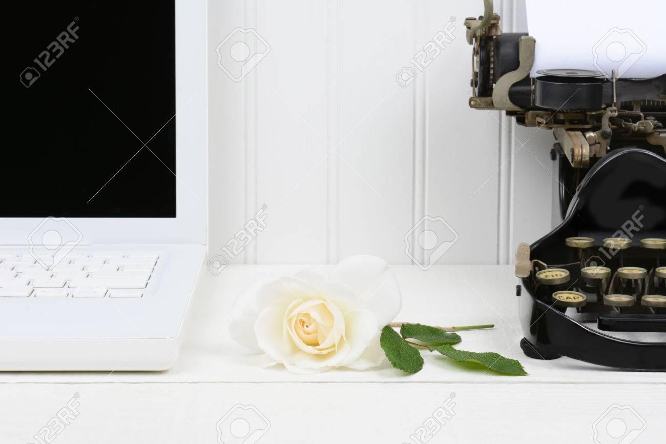 Gros plan d un bureau blanc avec une rose pose entre un ordinateur
