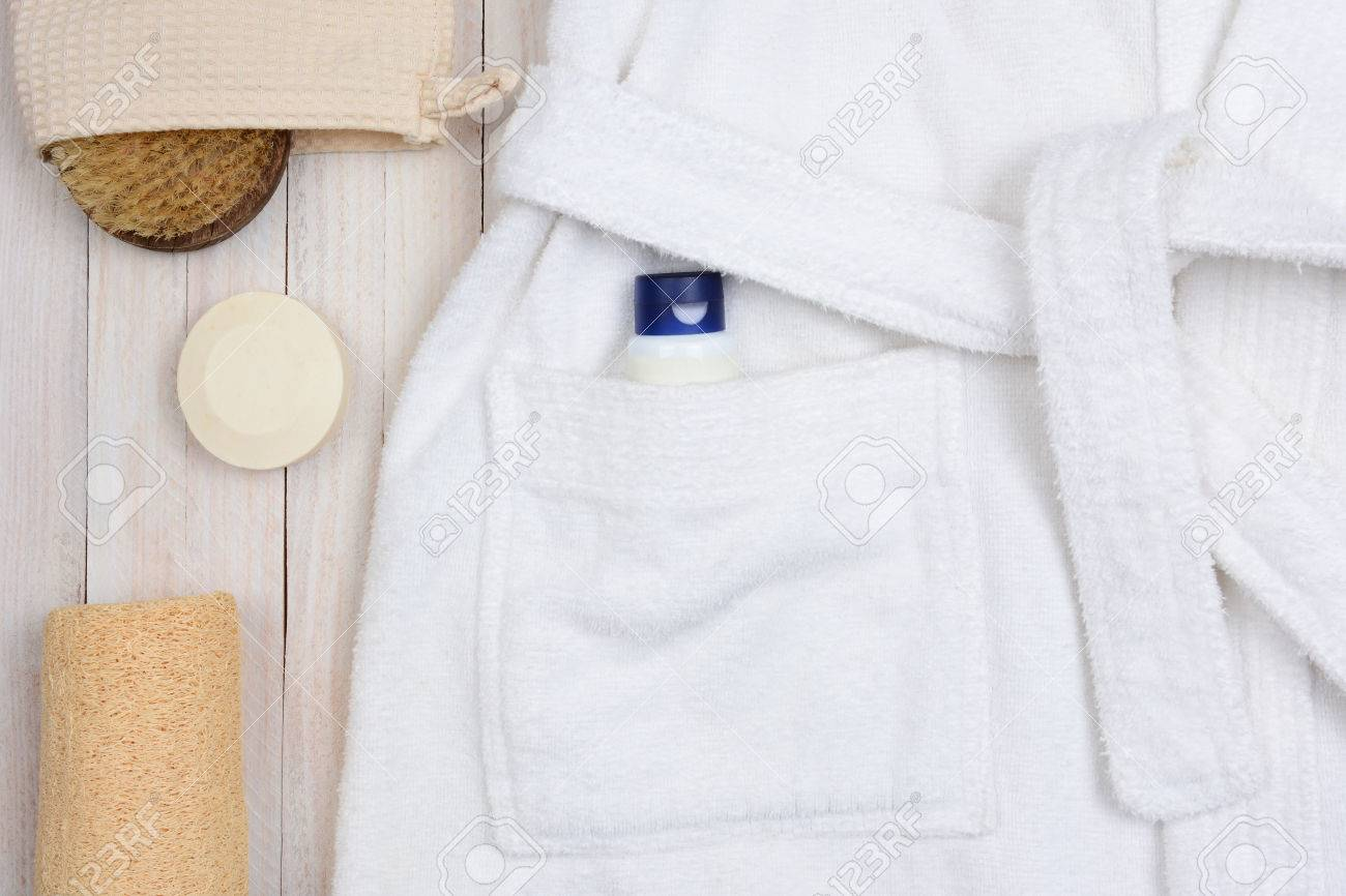 b61fb11a71 Closeup of a bathrobe with lotion in the pocket. A scrub brush and soap and