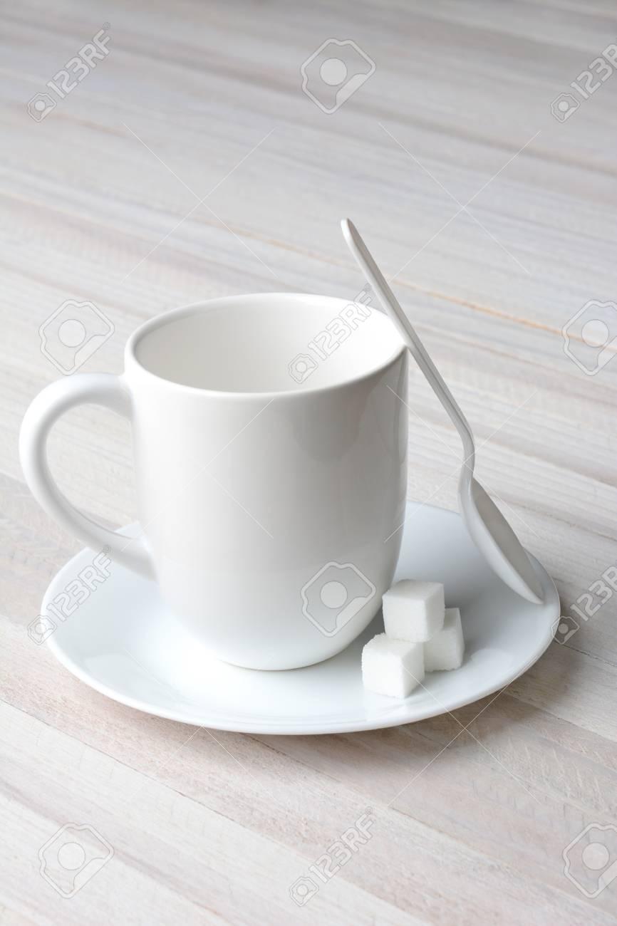 Primo piano di un cucchiaio di plastica bianca tazza di caffè bianco e  cubetti di zucchero bianco su un tavolo da cucina rustica imbiancata.  Formato ...